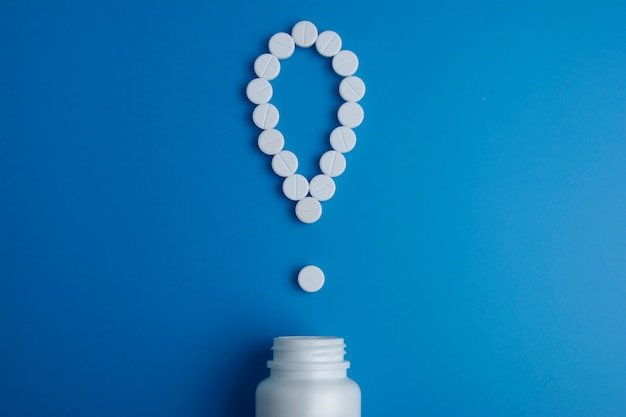 Signo de exclamación con pastillas vertidas de una botella de medicina. vista superior. endecha plana.