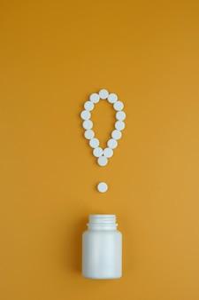 El signo de exclamación de las píldoras. signo de exclamación. píldoras blancas sobre un fondo amarillo. información importante sobre temas médicos.