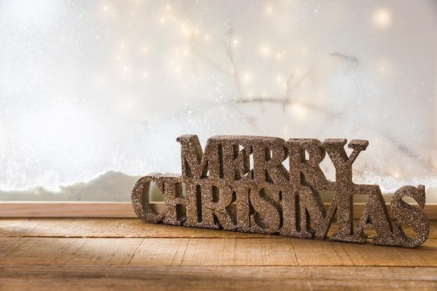 Signo de feliz navidad en la mesa de madera cerca del banco de nieve y luces de hadas