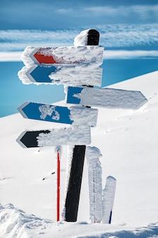 Signo de flecha en blanco cubierto de nieve en las montañas