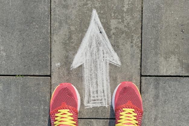 Signo de flecha pintado en la acera gris con piernas de mujer en zapatillas de deporte