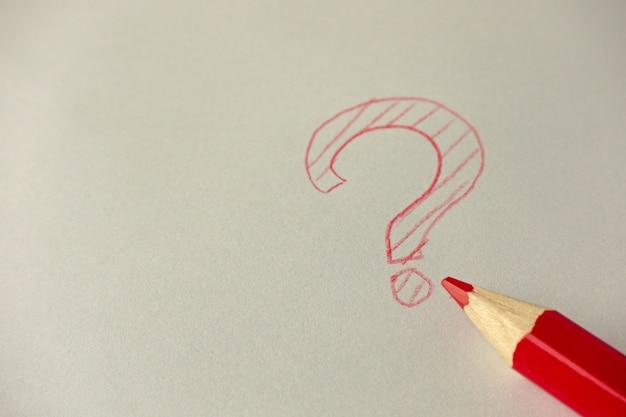 Signo de interrogación con lápiz de grafito rojo