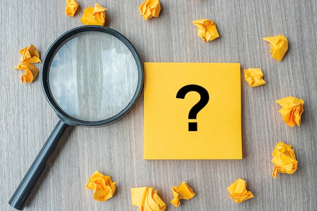 Signo de interrogación (?) palabra en nota amarilla con papel desmenuzado