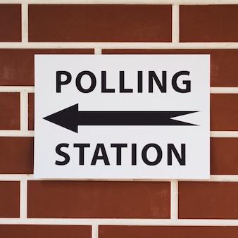 Signo de la mesa electoral con dirección en primer plano de la pared de ladrillo