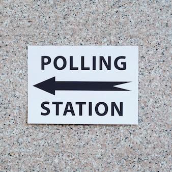 Signo de la mesa electoral con dirección en primer plano de la pared