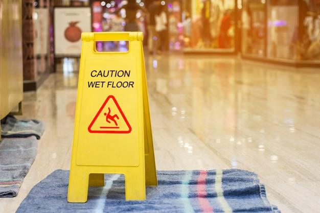 Signo que muestra advertencia de piso húmedo de precaución en la tienda de compras