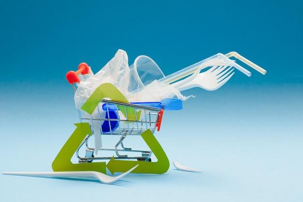 Signo de reciclaje de basura y basura de plástico diferente en una vista superior de fondo de color