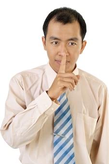 Signo de silencio con el dedo del empresario asiático cerca de los labios sobre fondo blanco.