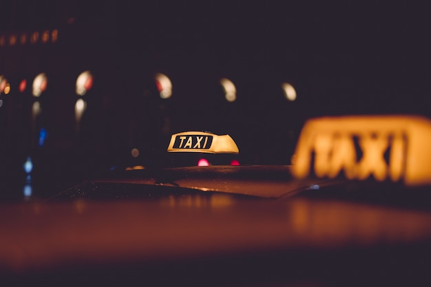 Signo de taxi en el fondo nocturno de la ciudad borrosa