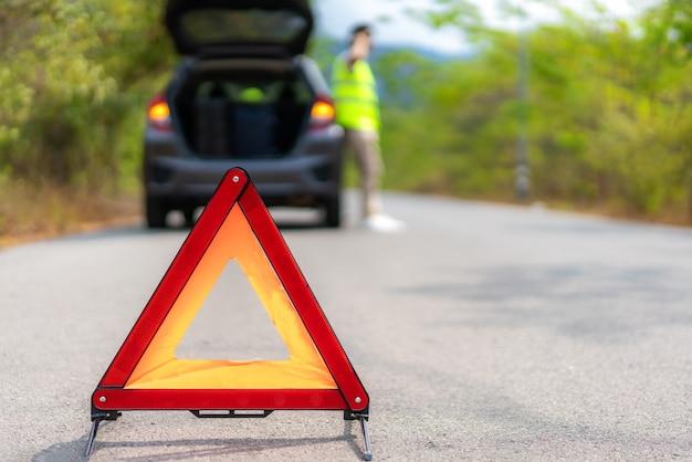 Signo de triángulo de avería en la carretera con hombre preocupado hablando por teléfono móvil con seguro