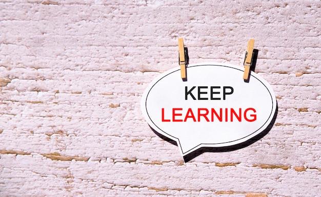 Sigue aprendiendo en un papel de burbuja blanco con alfileres de madera