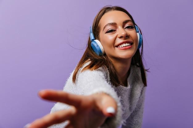 Sígueme. atractiva joven de 24 años llamando para acompañarla. estudiante en auriculares escucha una canción positiva mientras posa para el retrato