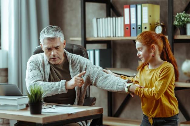 Sígueme. chica encantada positiva distrae a su padre del trabajo mientras quiere mostrarle algo