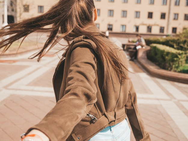 Sígueme concepto romántico mujer joven con el pelo largo al aire libre de la mano de su novio