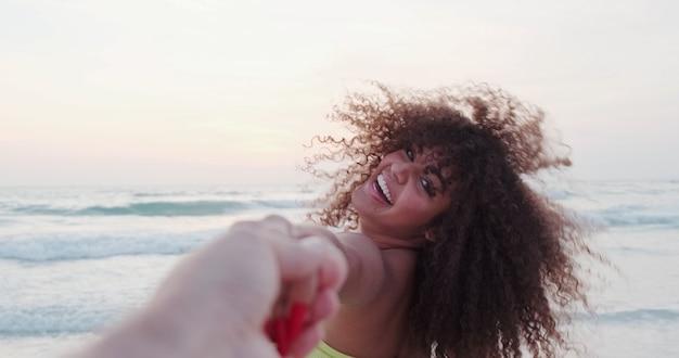 Sígueme foto de joven tirando de su novio en la orilla del mar vacaciones de verano o vacaciones pov