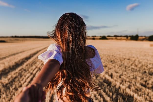 Sígueme. mujer joven de la mano y el hombre principal a la hermosa naturaleza puesta de sol paisaje amarillo