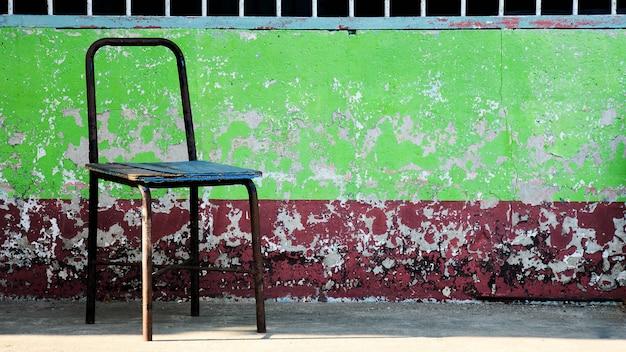 Silla de acero vieja y dañada en escuela rural.