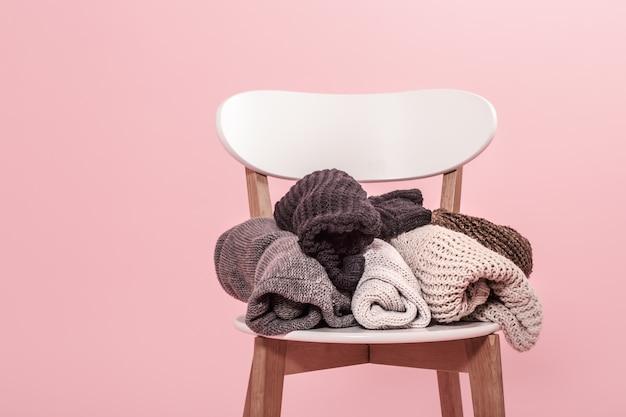 Silla blanca con una pila de suéteres de punto en una pared rosa