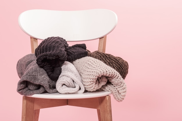 Silla blanca con una pila de suéteres de punto sobre un fondo rosa