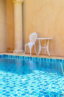 Silla blanca vacía y mesa al lado de la piscina