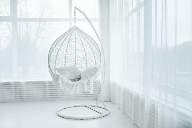 Silla colgante en interior sala blanca.