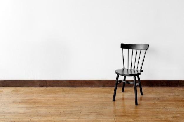 Una silla contra una pared blanca.