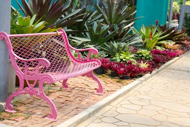 Silla de jardín rosa en el jardín.