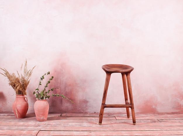 Silla de madera, jarras de barro con ramas en la mesa de la pared. interior de estilo retro vintage