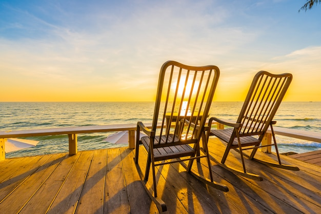 Silla de madera vacía y mesa en el patio al aire libre con hermosa playa tropical y mar