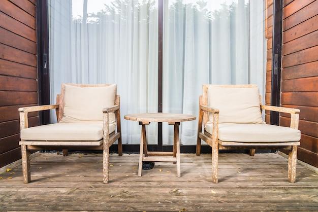 Silla y mesa de madera en terraza exterior.
