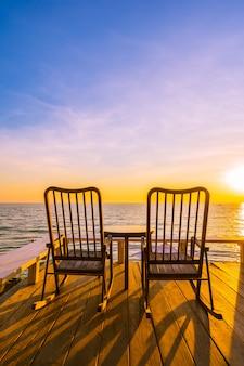 Silla y mesa de madera vacía en el patio al aire libre con hermosa playa tropical y mar