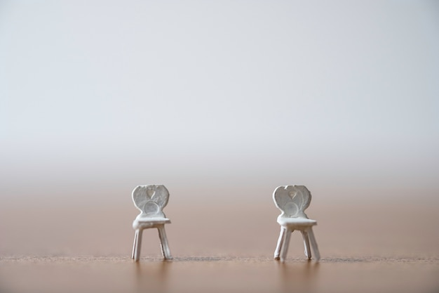 La silla en miniatura blanca mantiene la distancia en público y previene la infección pandémica del brote del virus corona covid-19. concepto de distanciamiento social.