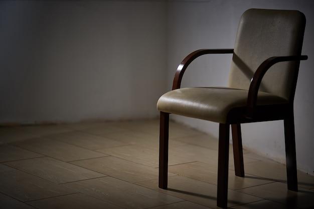 Una silla moderna vacía en un cuarto oscuro