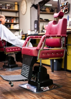 Silla de peluquería de cuero con cliente en segundo plano.