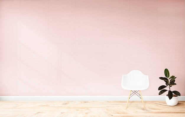 Silla y una planta contra una pared rosa.