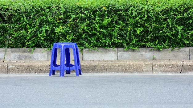 Silla plástica azul en la calle de asfalto.