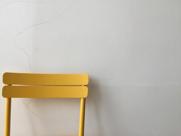 Silla de plástico amarilla contra una pared blanca.