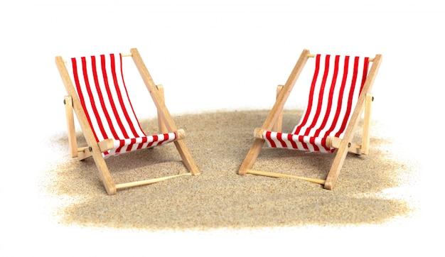 Silla de playa rayada en la arena aislada en la pared blanca