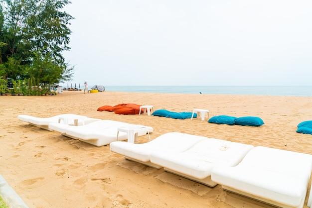 Silla de playa vacía sobre arena con fondo de mar océano
