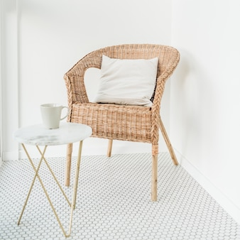 Silla de ratán con almohada y mesa de centro de mármol en el balcón con piso de mosaico