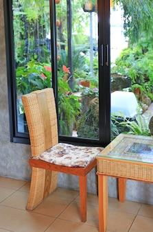 Silla de ratán y mesita en café natural cerca de la planta del jardín.