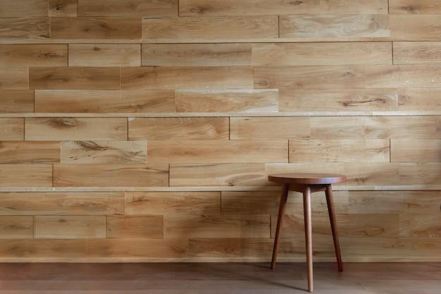 Silla redonda al lado de la pared de madera.
