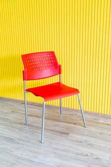 Silla roja con pared amarilla