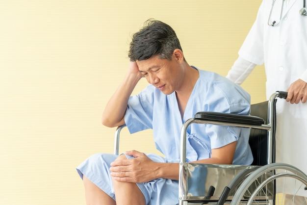 Silla de ruedas paciente mayor asiática con dolor de rodilla