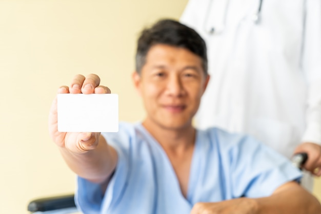 Silla de ruedas paciente mayor asiática que sonríe con la tarjeta de crédito