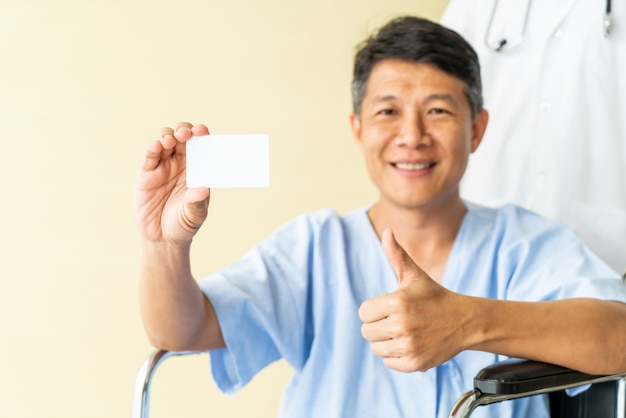 Silla de ruedas paciente senior asiático sonriendo con tarjeta de crédito
