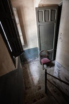 Silla solitaria en una habitación vacía y oscura.