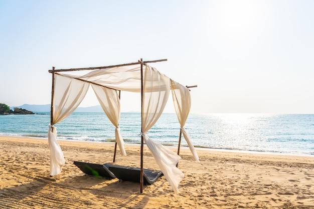 Silla sombrilla y salón en la hermosa playa mar océano en el cielo