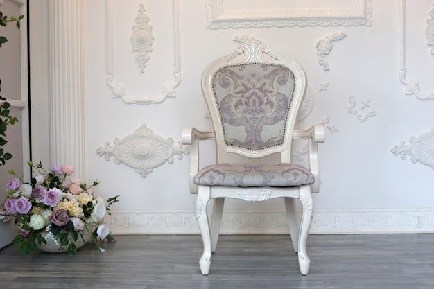 Una silla suave vintage se alza contra una pared blanca. silla de madera blanca antigua