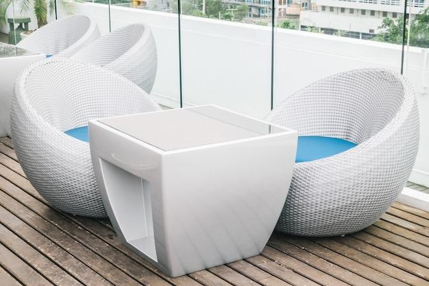 Silla vacía y mesa con terraza exterior.